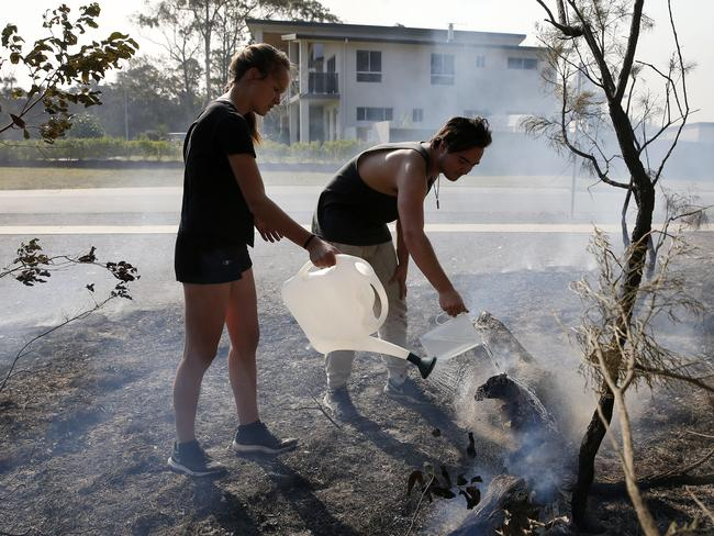 Brooke and Tristan Smith blacken out bush near their home at Wallaby Point, NSW, Saturday, November 9, 2019. Two people have been killed and seven others are missing in bushfires in NSW which have also destroyed at least 100 homes. (AAP Image/Darren Pateman)