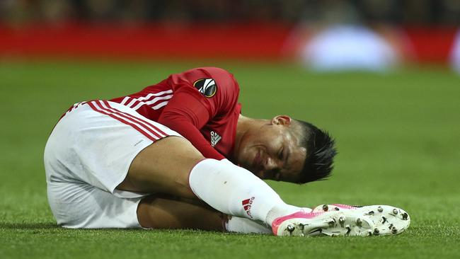Manchester United's Marcos Rojo holds his knee.