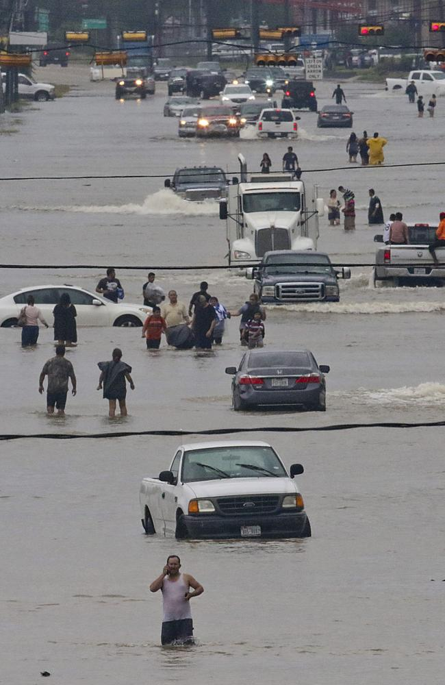 People walk through the flooded waters in Houston as city battles with tropical storm Harvey and resulting floods. Picture: AFP