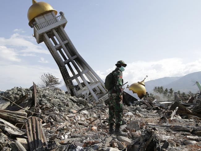 An Indonesian trooper stands beside a toppled mosque in Central Sulawesi, Indonesia on October 6, 2018. Picture: AP