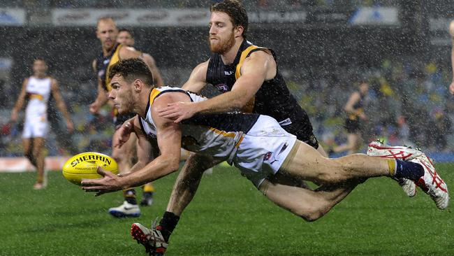 Eagle Luke Shuey dishes off a handball under pressure from Reece Conca. Picture: Daniel Wilkins