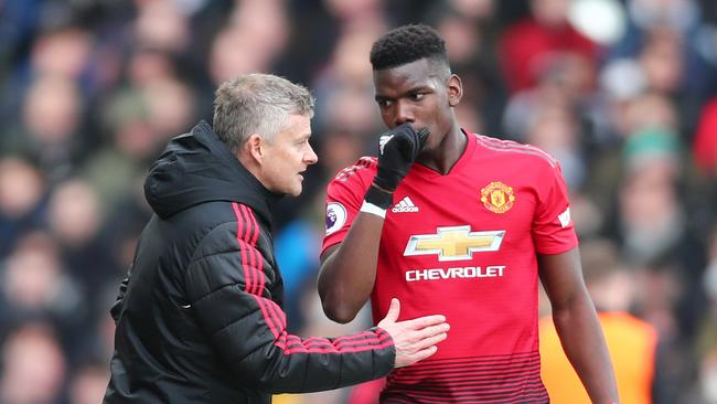 Ole Gunnar Solskjaer, Interim Manager of Manchester United talks with Paul Pogba