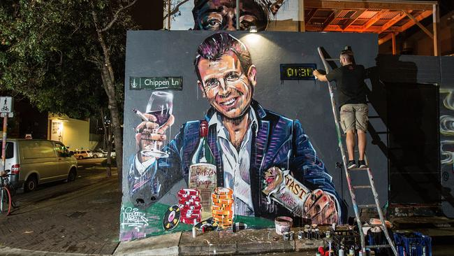 Artist Scott Marsh paints a mural of Premier Mike Baird holding a kebab and glass of wine surrounded by poker chips commenting on the Sydney lockout laws. Picture: Cole Bennetts/Getty Images