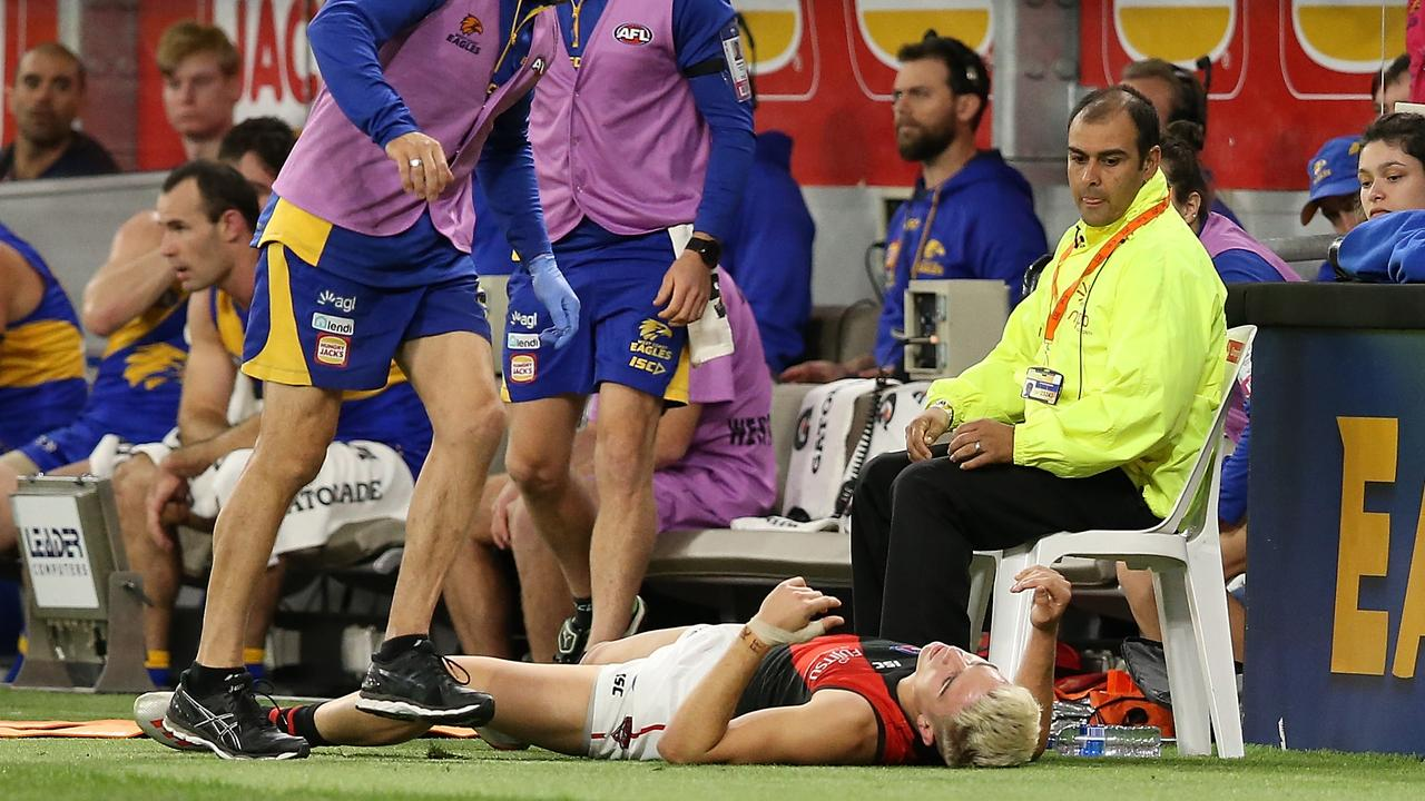 Matt Guelfi lies on the ground after hitting the fence at Optus Stadium.