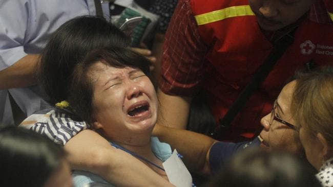 Grief stricken relatives of passengers of the missing AirAsia flight QZ 8501 react to the news on television of bodies found near the site where the jetliner disappeared. Pic: AP Photo/Trisnadi, File.