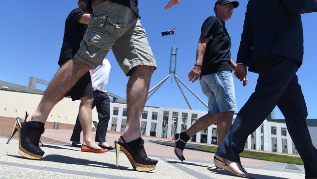 Male Bureaucrats of the Department of Foreign Affairs and Trade take part in the 'Walk a mile in her shoes' campaign outside Parliament House. Picture: AAP Image/Lukas Coch)