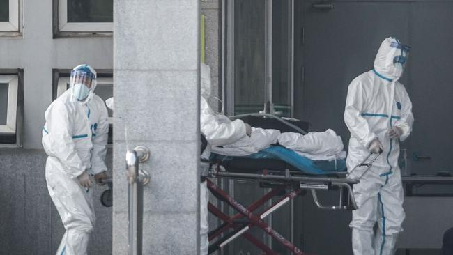 Medical staff members carry a patient into the Jinyintan hospital on January 18, 2020. Picture: STR / AFP