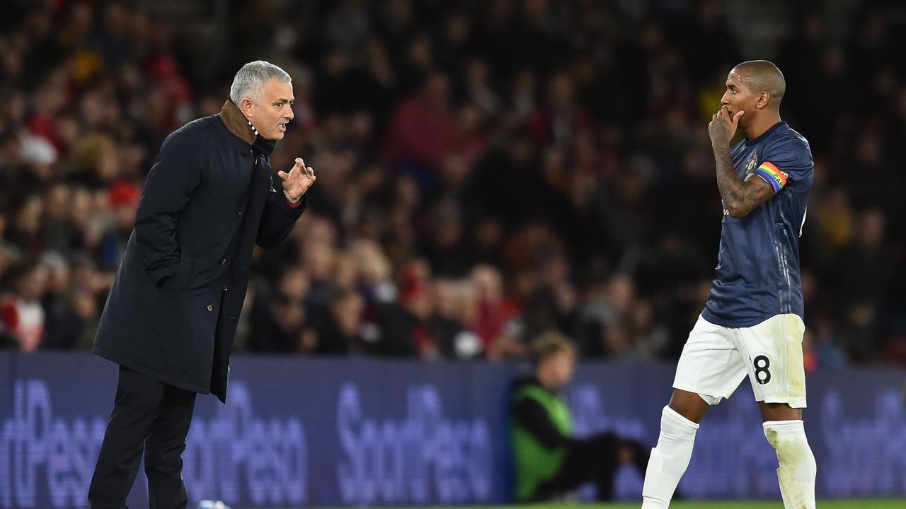 Manchester United's Portuguese manager Jose Mourinho (L) talks to Ashley Young (R)