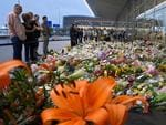 People look at flowers placed in remembrance for the victims of the MH17 plane crash at Schiphol Airport, near Amsterdam, on July 21, 2014. Western powers on July 21 ratcheted up the pressure on Moscow over the Malaysian plane disaster, as a train loaded with some 280 bodies was finally allowed to leave a rebel-held station four days after the jet crashed in strife-torn east Ukraine. AFP PHOTO / JOHN THYS