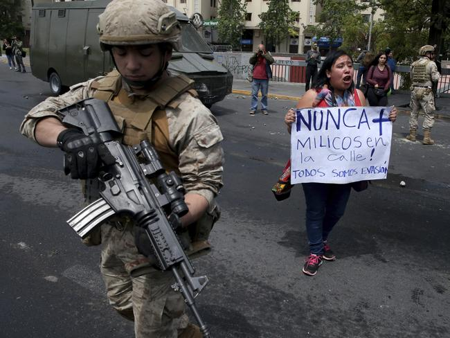 """A woman holds a sign next to a soldier that reads in Spanish """"Never again army in the streets"""" after a night of riots that forced a state of emergency. Picture: AP Photo"""
