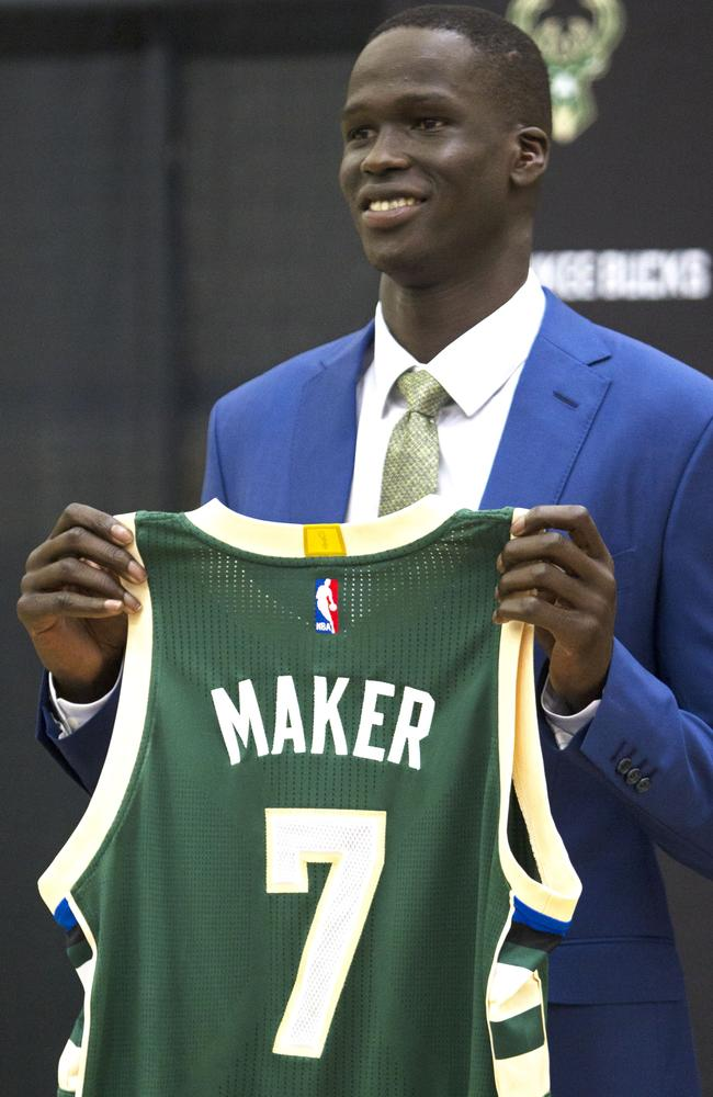 Milwaukee draft pick Thon Maker holds up his Bucks jersey.