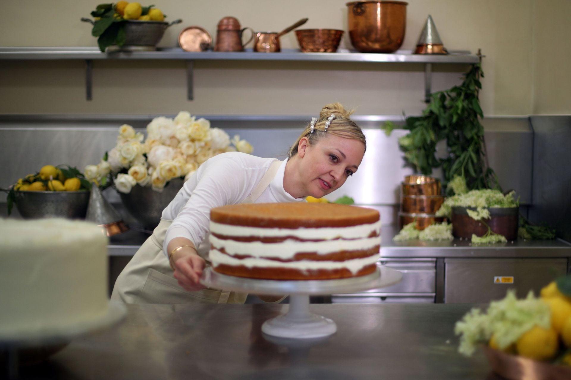 Violet Bakery's Claire Ptak and a tier of the wedding cake in the kitchens of Buckingham Palace. Image credit: Getty Images