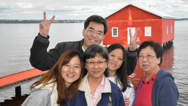 Singaporean Charlotte Chan (left) poses for a photograph with her family against the Crawley Edge Boatshed in Perth. Picture: AAP/Rebecca Le May