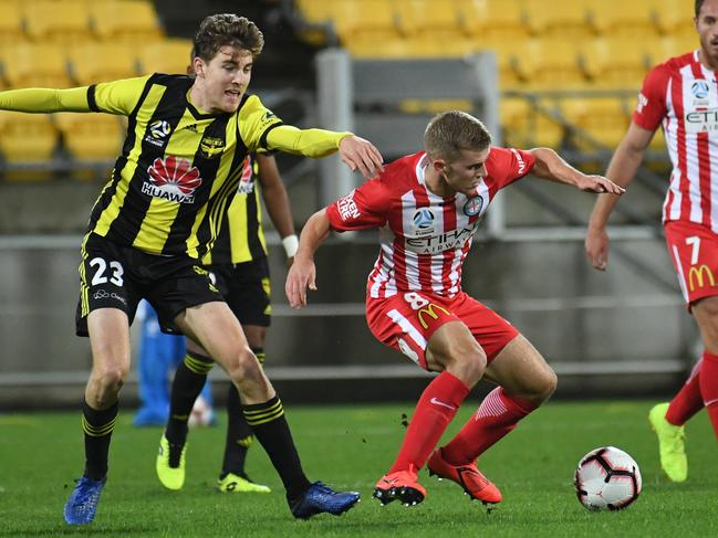 Melbourne City's Riley McGree plays the ball in front of Wellington's Max Burgess on Sunday. Picture: AAP