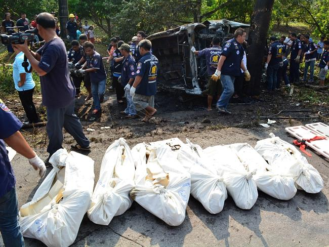 Thai rescue workers carry bodies of people killed in a road accident in Chanthaburi. They were returning home for the Buddhist New Year
