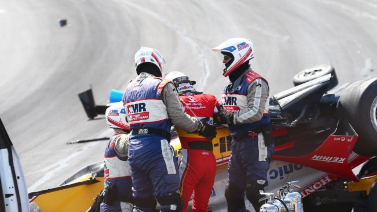 Takuma Sato is helped from his wrecked car.