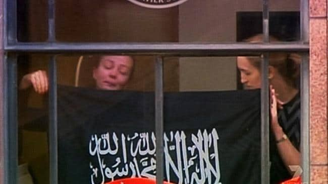 Survivor Marcia Mikhael in the window of the Lindt Cafe during the siege with Katrina Dawson (right) who was killed as the standoff came to an end.