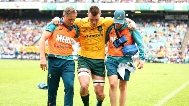 Jack Dempsey of the Wallabies is helped from the field at Allianz Stadium.