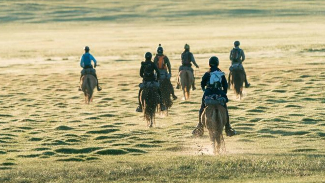 Mongol Derby riders crossing flat grassland in Mongolia. Much of the race is on sand dunes and through frozen mountains. Picture: Twitter @mongolderbylive