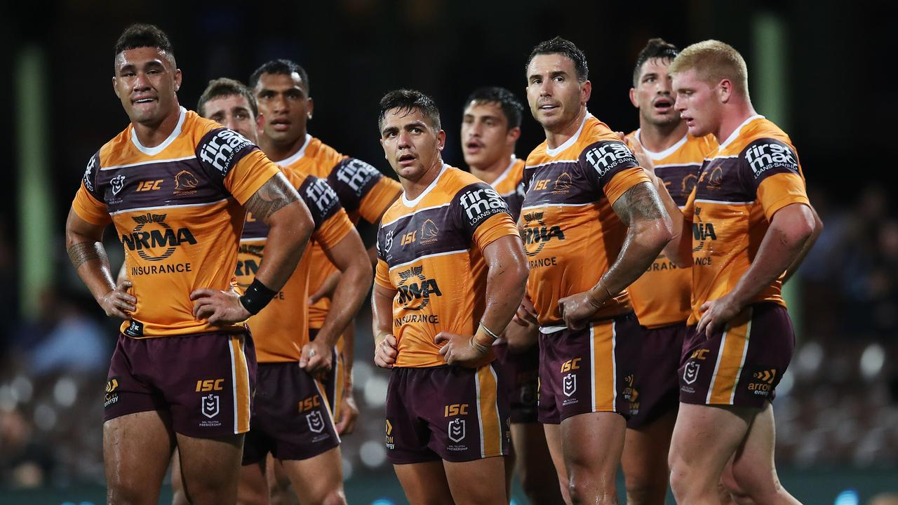 Dejected Broncos players try to digest their record thrashing at the hands of the Roosters at