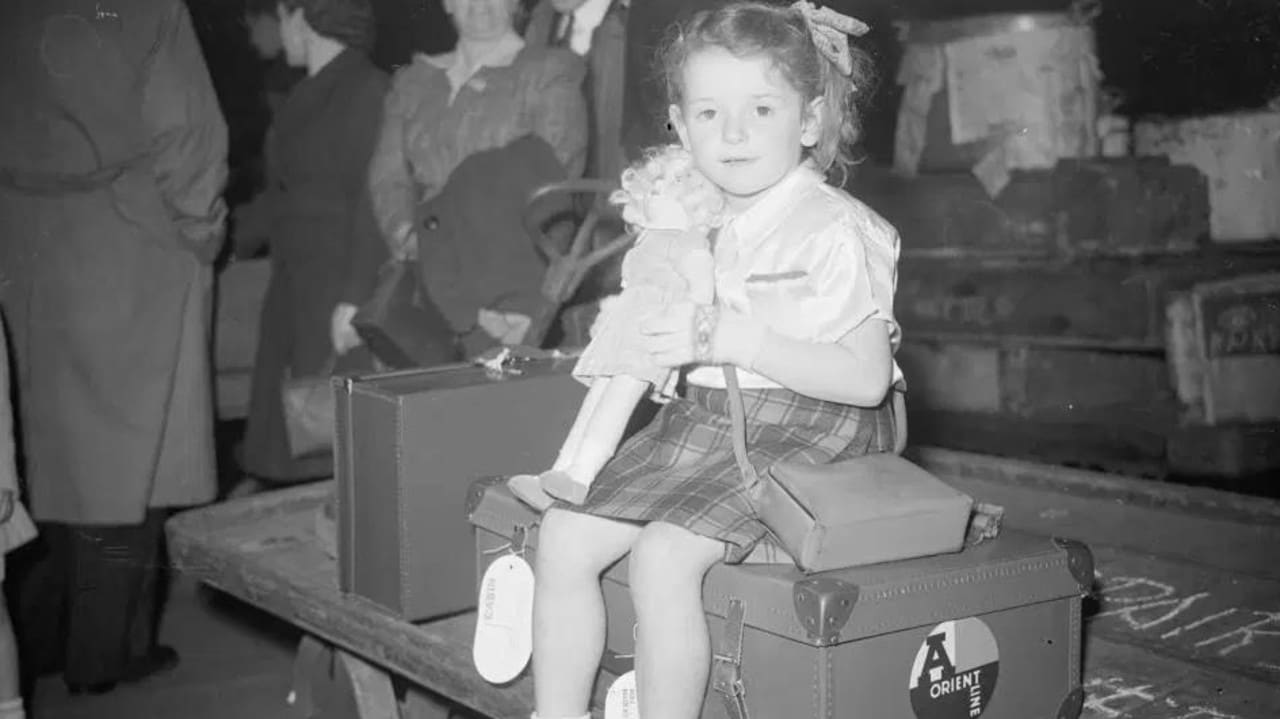 A girl waiting with all her belongings for her train to Tilbury, UK, where she, along with 1100 others, would set sail to Australia.