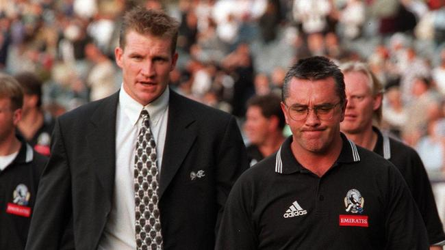 An injured Nathan Buckley walks with Tony Shaw during his last season as Collingwood coach.