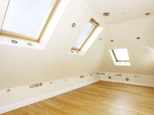 One of the bedrooms features several downlights despite the skylights.