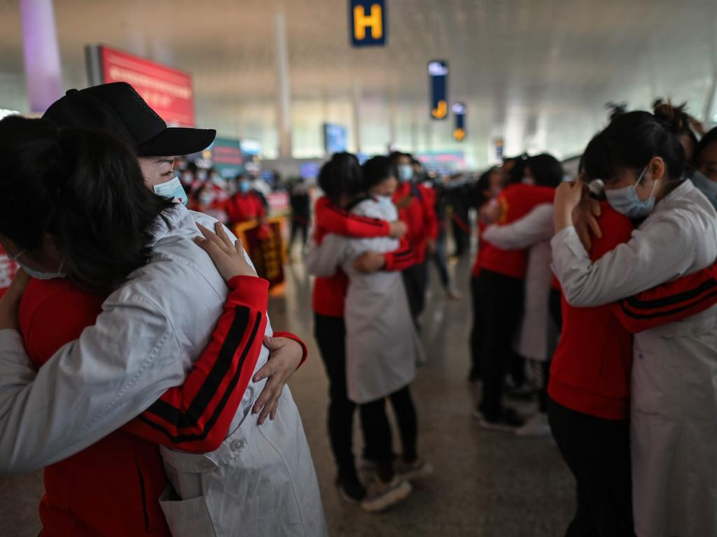 Medical staff hug after working together during the COVID-19 coronavirus outbreak during a ceremony before leaving Wuhan. Picture: AFP