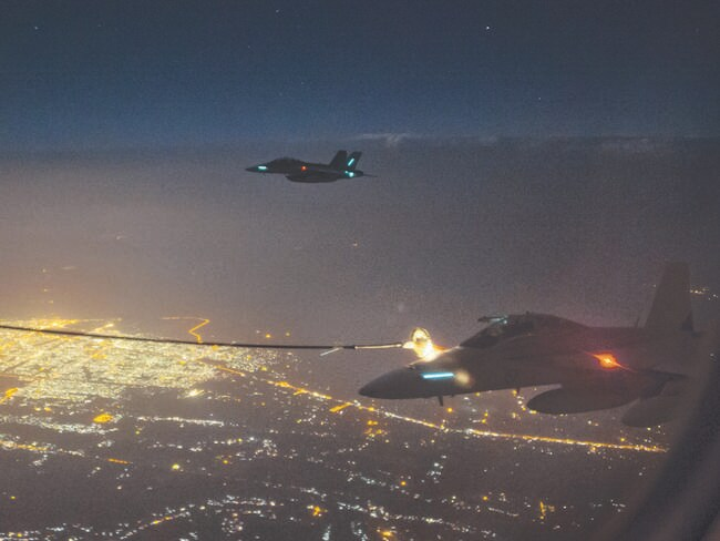 On a mission ... two Royal Australian Air Force (RAAF) F/A-18F Super Hornet aircraft conduct air to air refuelling with a RAAF KC-30A Multi Role Tanker Transport aircraft by night over the skies of Iraq.