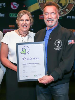 Herald and Weekly Times and Good Friday Appeal chairwoman Penny Fowler presents Arnold Schwarzenegger with a certificate of thanks. Picture: Tim Carrafa