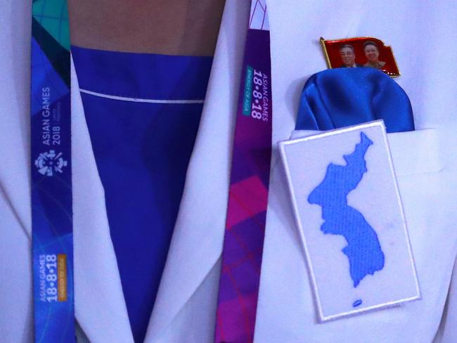 A combined Koreas athlete from North Korea wears a pin of late North Korean leaders Kim Il Sung and Kim Jong Il. Picture: AP
