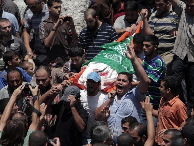 Strikes ... Mourners chant angry slogans during the funeral of Palestinian Widad Mustafa Deif, 27, who was killed along with her son Ali Mohammed Deif in Israeli strikes in Gaza City. Widad was the wife of Mohammed Deif, the leader of the Hamas military wing. Picture: AP