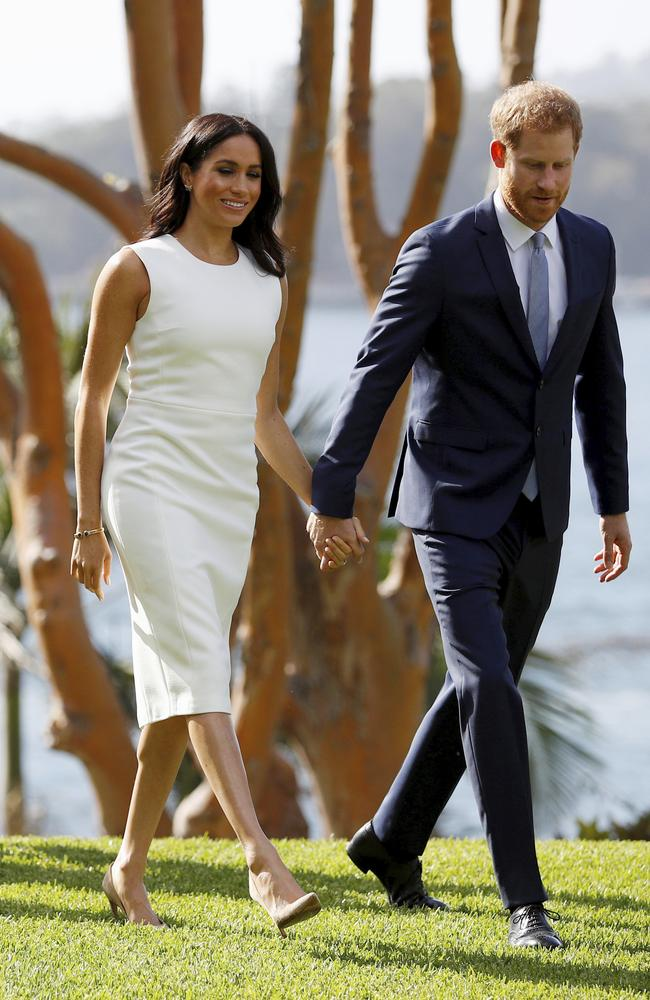 Britain's Prince Harry and Meghan, Duchess of Sussex walk hand-in-hand at Admiralty House.