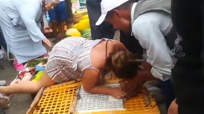 Shocking footage shows the woman biting the trader's fingers.