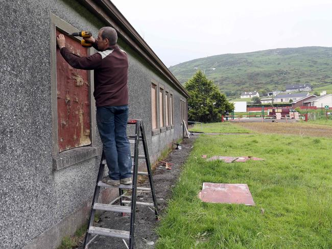 A workman tidies up a closed customs post at the border between Newry in Northern Ireland and Dundalk in the Republic of Ireland. Picture: AFP/Paul Faith