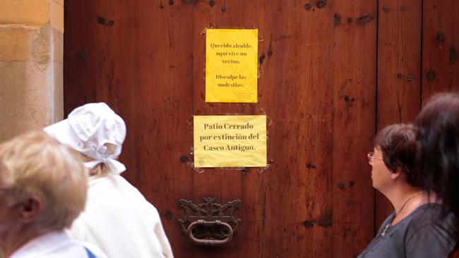 """Tourists walk past signs posted on a closed grand house entry in Palma, Majorca, which reads: """"Dear major, here live a neighbour. Sorry for the inconvenience"""" and """"Closed courtyard due to extinction of the Old Town"""". Picture: Reuters/Enrique Calvo"""
