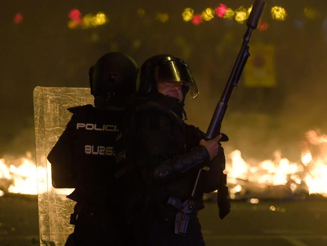 Anti-riot police officers stand guard in front of a barricade, which went up in flames. Picture: AFP
