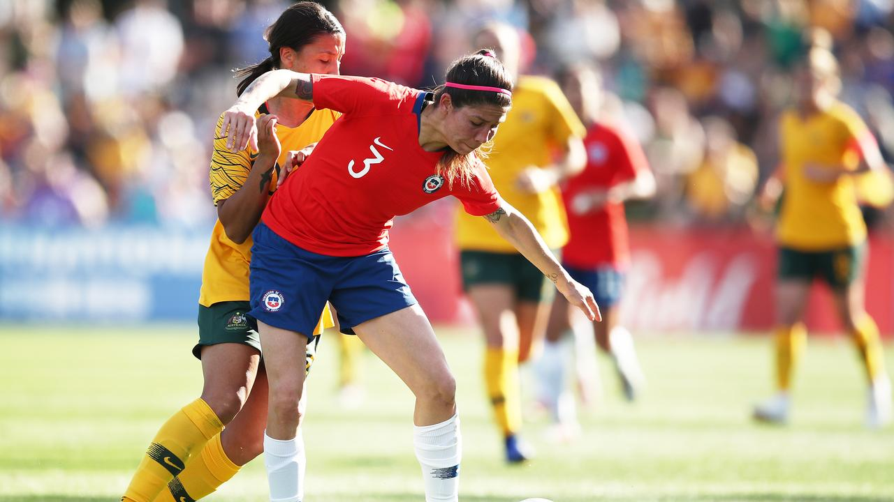 Carla Guerrero of Chile is challenged by Samantha Kerr.