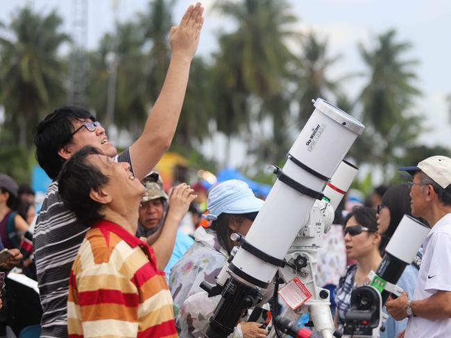 Skywatchers gather to watch the moon as it moves in front of the sun in Malaysia. Picture: AFP