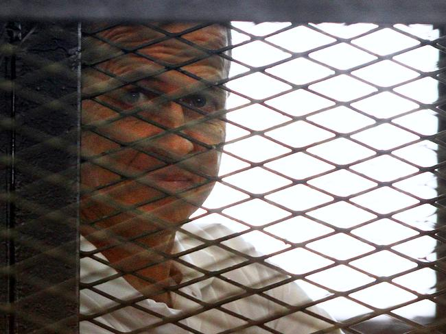 International outcry ... Australian Al-Jazeera journalist Peter Greste looks out from the defendant's cage during his sentencing hearing in a courtroom in Cairo on June 23. Picture: AP