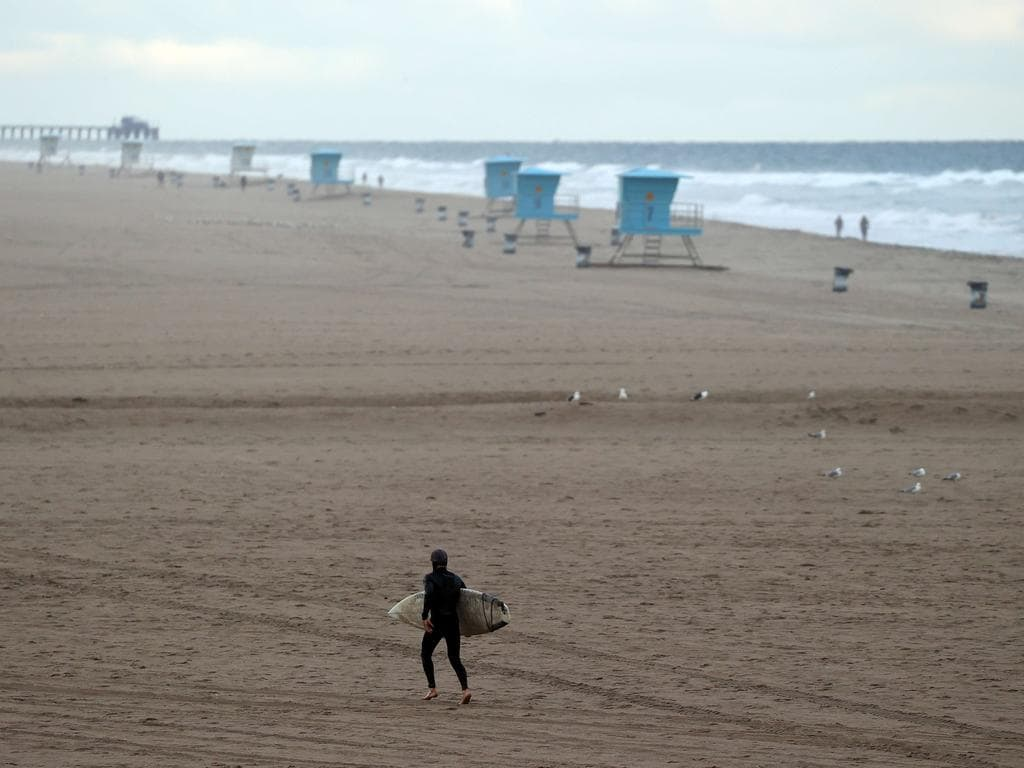 A surfer walks on the beach in Huntington Beach, California. Picture: Getty