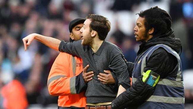 A pitch invader is handled by security