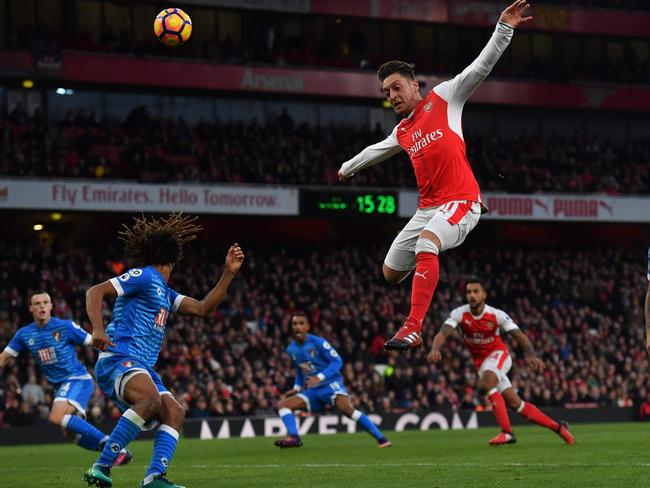 Arsenal's German midfielder Mesut Ozil (C) leaps for the ball.