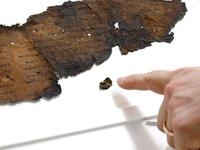 To the naked eye, this small scroll fragment is unreadable. But new technology reveals it contains hidden text. Picture: AFP