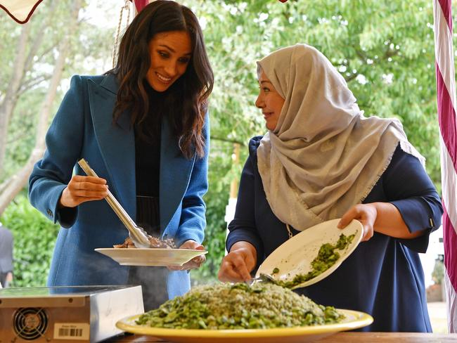 Meghan, Duchess of Sussex helps to prepare food at the launch of a cookbook. Picture: AFP