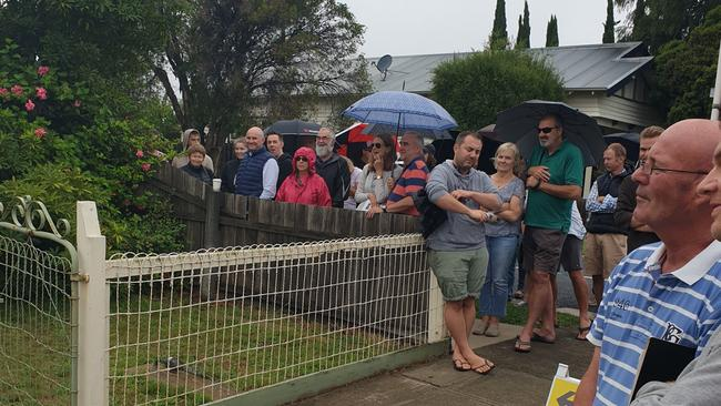 Umbrellas were the order of the day at the auction of 114 Elizabeth Street, Geelong West.
