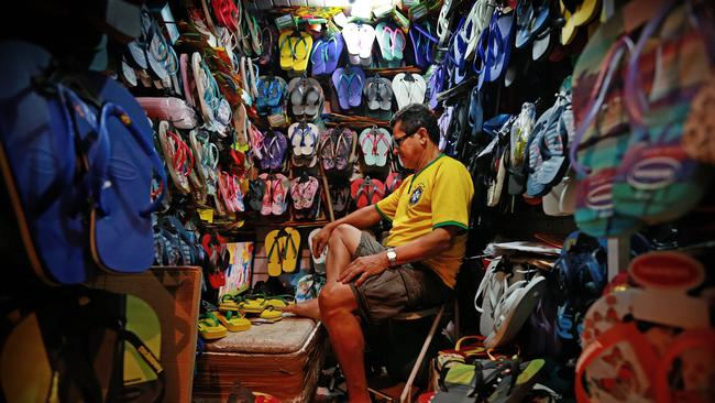 Local thong seller of Rocinha watches the game in on a tiny TV in his stall at the markets.