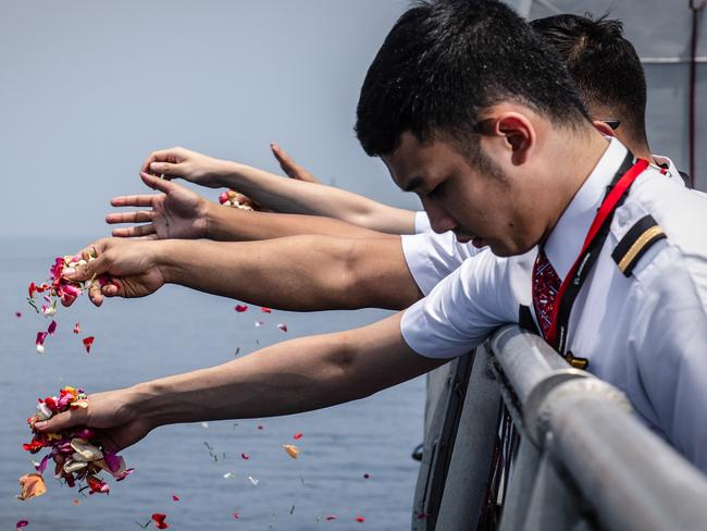 Colleagues of victims of Lion Air flight JT 610 throw flowers on deck of Indonesian Navy ship KRI Banjarmasin during visit and pray at the site of the crash. Picture: Getty