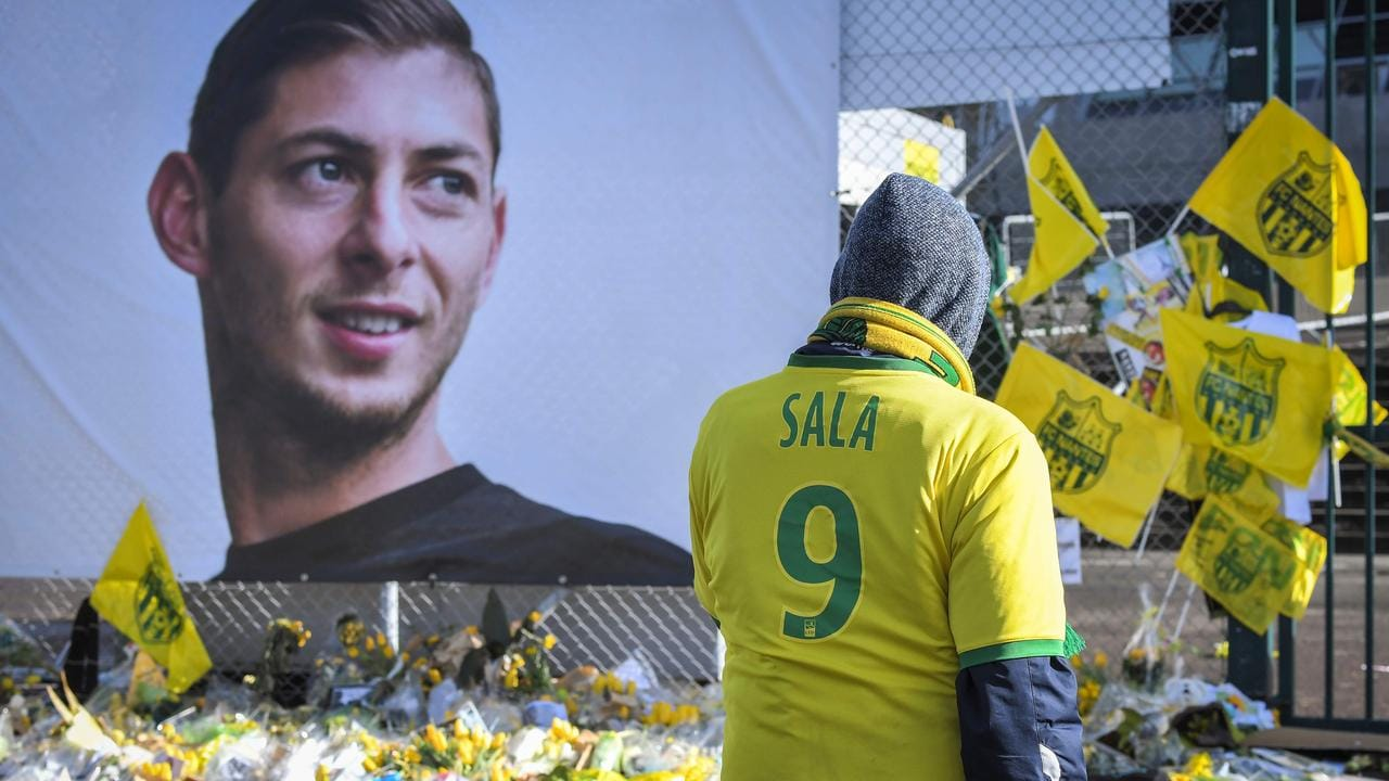 Supporters pay tribute and look at yellow flowers displayed in front of the portrait of Argentinian forward Emiliano Sala at the Beaujoire stadium in Nantes.
