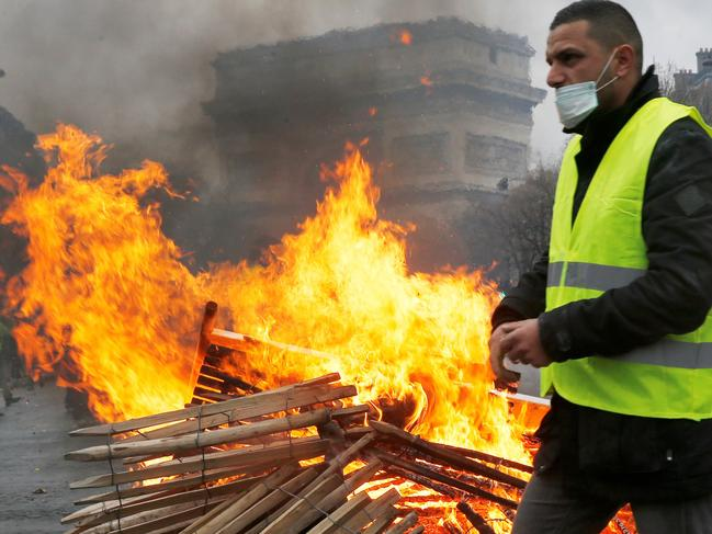 A demonstrator walks past a fire during a protest of Yellow vests (Gilets jaunes) against rising oil prices and living costs, near the Arc de Triomphe, in Paris. Picture: AFP